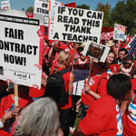 "Striking Chicago teachers and their supporters attend a rally at Union Park. One visible poster reads ""If you can read this thank a teacher."" Another poster reads ""Fair contract now!"""