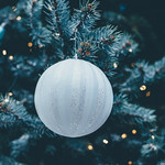 Closeup of a Christmas tree hung with white and blue ornaments and string lights