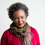 a photo of Claudia Rankine, an older darkskinned woman with a gray, short afro, wearing a pink shirt and multicolored scarf