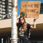 """White woman with long brown hair wearing a black t-shirt holds a cardboard sign that reads """"We Are The Change"""" as she stands amid a protest."""