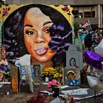 a memorial depicts an illustration of Breonna Taylor, a Black woman with shoulder-length black hair, among candles, teddy bears,