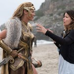 a white woman in gold armor stands on a beach with a white woman director with brown hair