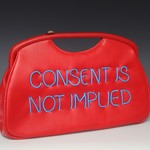 a photo of a red pursue that has Consent Is Not Implied embroidered in neon light