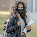 A Black woman with long, black, curly hair, stands on a college campus in a mask, touting books in her arms