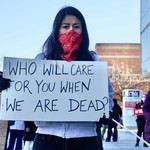 "A nurse with short dark hair stands outside holding a sign that reads, ""Who will care for you after we are dead?"""