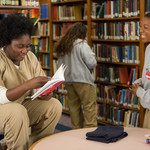 two Black women who are incarcerated talk in the library on Orange is the New Black