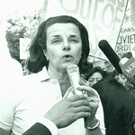 Dianne Feinstein, a white woman with short, black hair, speaks into a microphone in San Francisco in the 1970s as protestors stand around her