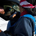 a Black woman helps another Black woman fill out her ballot while she sits in a car