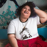 Jude Valentin, a plus-size person of color, sits on the ground in a red skirt and smiles at the camera