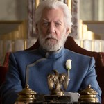Donald Sutherland as President Coriolanus Snow, an elderly white man sitting behind a desk with a crown sitting on top of it, in The Hunger Games