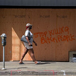 a Black woman walks past a boarded up store while wearing a mask in Los Angeles, California