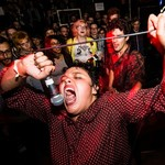 a lightskinned person wearing a red polka dot shirt and screaming into a microphone as a crowd surrounds them