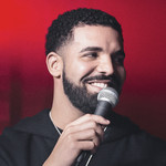 Drake holding a microphone to his mouth and smiling, looking to the right, against a red background
