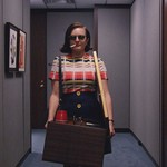 a white woman smoking a cigarette walks through an office with a box