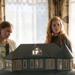 two white women stand in front of a dollhouse on Sharp Objects