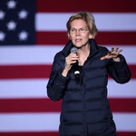 Elizabeth Warren, a white woman with short blond hair, stands in front of a USA flag