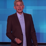 Ellen DeGeneres, a white woman, wears a suit and stands in front of a blue screen. Her hair is blond and short and she's gesturing with a serious look on her face.