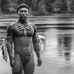 a dark-skinned, dark-haired man in a loincloth stands in a river, looking toward the camera