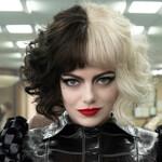 Emma Watson plays Cruella, a white woman with a half black, half white bob cut and red lipstick, in Cruella