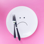 An empty plate with silverware and a sad face drawn on it against a pink background