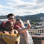 Three plus-size people on a rooftop with city view taking a selfie with a cell phone