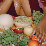 image of a fat brown woman, from the neck down, wearing a raspberry-colored velvet top, and touching an assortment of fruit