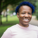 Felix Ever After author Kacen Callender, who is Black and nonbinary and smiles directly at the camera while wearing a pink tee, has blue hair.