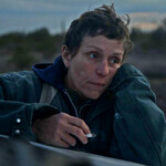 Frances McDormand plays Fern, a white woman with short, brown hair stares off in the distance while smoking a cigarette in Nomadland