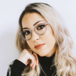 Gabriela Garcia, a light-skinned Latinx woman with long blond hair and in gray plastic glasses, leans her head against her hand