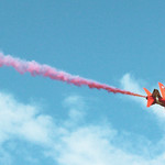 A red jet against the blue sky, pink smoke trailing behind it