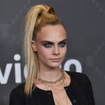 Cara Delevingne arrives at a fashion show. She is white with long blond hair in a high ponytail. She wears black and heavy eyeliner.