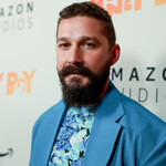 Shia LaBeouf, a white guy with brown hair and a messy beard, wears a blue suit.