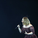 Adele, a white woman with short, red hair, bends over and belts into a microphone