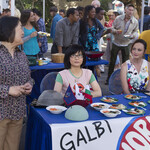 Mrs. Kim smiling (left), Lane Kim looking alert (middle), and Rory Gilmore smiling (right) at a food-serving table with paper plates of Korean galbi