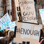 "Various gun reform posters at a rally that say things like ""#ENOUGH"" and ""Teacher for Gun Reform"""
