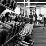 Black and white photo of a dumbbell rack at a gym and a person lifting in the background