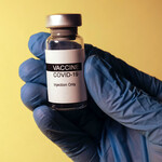 Blue gloved hand holding vial of Covid-19 vaccine