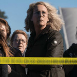 Jamie Lee Curtis as Laurie Strode stands with a crowd behind police tape and stares off screen