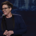Hannah Gadsby smiles at the audience and grips a microphone stand with both hands during her Netflix comedy special