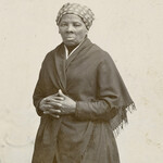 Harriet Tubman, a dark-skinned Black woman wearing a headscarf and a black shawl, poses with her hands crossed in front of her