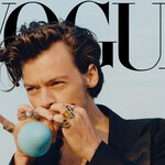 Harry Styles, a young white man with short brown hair, blows into a balloon on the cover of Vogue