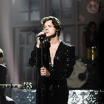 Harry Styles performs onstage at SNL wearing a sparkly black jumpsuit and a long necklace.