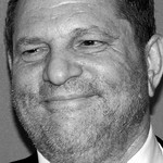 A black and white photo of Harvey Weinstein smiling