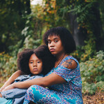 a photo of a Black woman with an afro holding her Black child, who also has an afro, as they sit on the floor of a forest