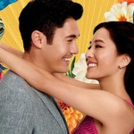 An Asian couple embrace in front of a teal and yellow background