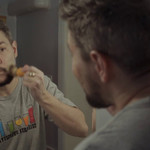 Henry Sias looking into the mirror while using a shaving brush on his beard