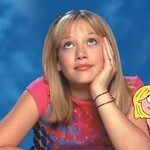 A white thirteen year old girl with blond hair and bangs sits next to a cartoon version of herself.