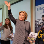 Hillary Clinton and Chelsea Clinton, two white women with blond hair, wave at a crowd during a book tour