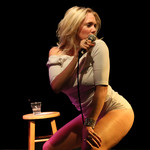 Jacqueline Frances, a white woman with short, blond hair, bends at the knees while standing on a stage with a microphone