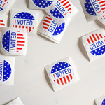 """Red, white, and blue """"I voted!"""" stickers spread out on a white surface"""